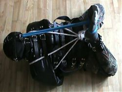 Muzzled slave is hogtied in the straitjacket